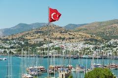 Vue à la marina avec le drapeau national turc au mât de drapeau ondulant au-dessus d'une colline dans Bodrum, Turquie Image stock
