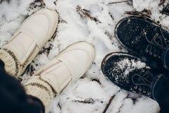 Vue à partir de dessus aux chaussures de couples dans la neige sur la terre en parc d'hiver Image libre de droits