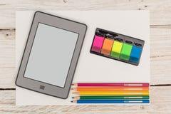 Vue à partir du dessus : ebook, autocollants et crayons colorés Photo libre de droits