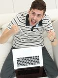 Vue à partir du dessus jeune homme radieux avec l'ordinateur portable se reposant sur le divan photographie stock libre de droits