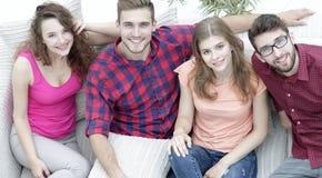 Vue à partir du dessus les quatre amis rient, se reposant sur le sofa Images stock