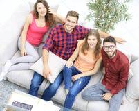 Vue à partir du dessus les quatre amis rient, se reposant sur le sofa Image libre de droits