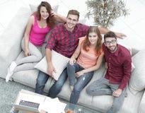 Vue à partir du dessus les quatre amis rient, se reposant sur le sofa Image stock