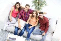 Vue à partir du dessus les quatre amis rient, se reposant sur le sofa Photos stock