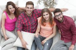 Vue à partir du dessus les quatre amis rient, se reposant sur le sofa Photographie stock libre de droits