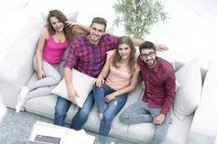 Vue à partir du dessus les quatre amis rient, se reposant sur le sofa Images libres de droits