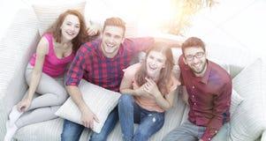 Vue à partir du dessus les quatre amis rient, se reposant sur le sofa Photos libres de droits
