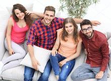 Vue à partir du dessus les quatre amis rient, se reposant sur le sofa Photographie stock