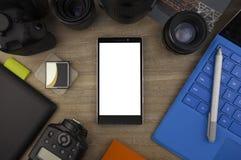 Vue à partir du dessus sur le smartphone, le PC de comprimé, l'objectif de caméra, le dslr et les accessoires de photo photographie stock libre de droits