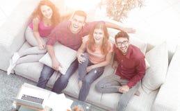 Vue à partir du dessus un groupe d'amis riants s'asseyant sur le sof Images stock