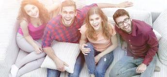 Vue à partir du dessus un groupe d'amis riants s'asseyant sur le sof Image libre de droits