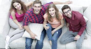 Vue à partir du dessus un groupe d'amis riants s'asseyant sur le sofa Photo stock