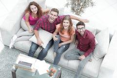Vue à partir du dessus un groupe d'amis riants s'asseyant sur le sofa Image libre de droits