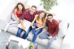 Vue à partir du dessus un groupe d'amis riants s'asseyant sur le sofa Images libres de droits