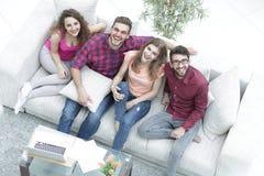 Vue à partir du dessus un groupe d'amis riants s'asseyant sur le sofa Photo libre de droits