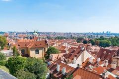 Vue à travers les dessus de toit oranges des bâtiments de Prague et de ville dessous Photographie stock