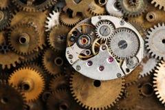 Vue âgée de macro de mécanisme d'horloge La rétro main observe des parties sur le fond de vitesses de bronze Image stock
