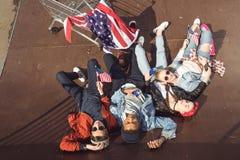 Vue élevée des adolescents ayant l'amusement et se situant avec le drapeau américain dans le parc de planche à roulettes Photo libre de droits