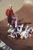 Vue élevée des adolescents ayant l'amusement et se situant avec le drapeau américain dans le parc de planche à roulettes Images libres de droits