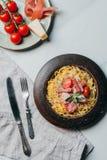 vue élevée des plats avec des tomtatoes de pâtes et de jamon, de parmesan et de cerise sur la table de marbre avec la serviette d photos stock