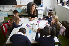Vue élevée du maître d'école primaire féminin s'asseyant à la table dans une salle de classe avec des écoliers pendant une leçon images libres de droits