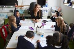 Vue élevée du maître d'école primaire féminin s'asseyant à une table dans une salle de classe avec des écoliers soulevant leurs m images libres de droits