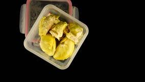Vue étendue ou supérieure plate de fruit crémeux de durian à l'intérieur de récipient en plastique dans le noir photos libres de droits