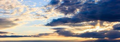 Vue étonnante de coucher du soleil avec les nuages foncés et les rayons de soleil d'or photographie stock