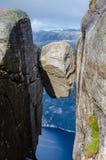 Vue étroite d'une roche de Kjeragbolten avec un fjord bleu Lysefjorden de la manière de fond dessous photos stock