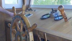 Vue étroite dans les carlingues du ` s de capitaine, l'équipement de navigation et la main du ` s de capitaine sur le gouvernail  Images stock
