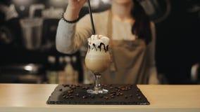 Vue étroite de barman femelle mettant une paille noire dans une boisson de café banque de vidéos