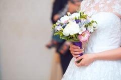Vue étroite de beau bouquet coloré de mariage dans une main d'une jeune mariée Image stock