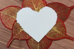 Vue étroite de coeur déchiré de livre blanc avec de l'or et les feuilles de papier rouges Image libre de droits