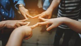 Vue étroite de jeunes amies de personnes avec des piles montrant l'unité et Photographie stock libre de droits