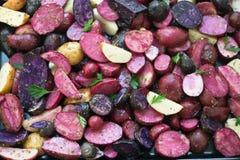 Vue étroite des pommes de terre pourpres et roses coupées en tranches crues Image stock