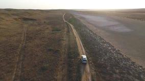Vue aérienne arrière : Grand SUV argenté conduisant dans une steppe devant le coucher du soleil banque de vidéos