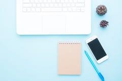 Vue aérienne d'espace de travail moderne avec l'ordinateur portable, le périphérique mobile et le carnet sur la couleur en pastel Photographie stock