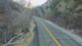 Vue aérienne d'un Canyon Road avec une conduite par le secteur boisé banque de vidéos