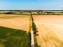 Vue aérienne d'un chemin de terre droit, qui est conçu comme avenue avec une rangée des arbres, à un village sur l'horizon photo libre de droits