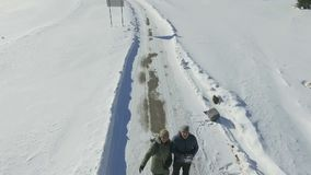 Vue aérienne d'un couple se tenant sur la route neigeuse d'hiver banque de vidéos