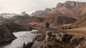 Vue aérienne d'un jeune couple se tenant au bord d'une falaise près d'un lac de montagne contre le contexte des roches épiques banque de vidéos