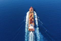 Vue aérienne d'un navire porte-conteneurs dans le mouvement au-dessus de l'océan ouvert photographie stock libre de droits