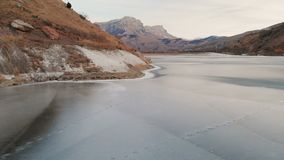 Vue aérienne d'un photographe de femme marchant le long du rivage d'un lac congelé de montagne contre le contexte des roches épiq banque de vidéos