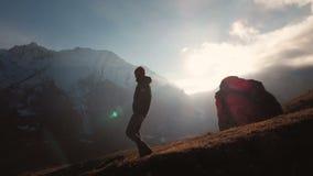Vue aérienne d'un tir épique d'un homme marchant au bord d'une montagne comme silhouette dans un beau coucher du soleil Silhouett banque de vidéos