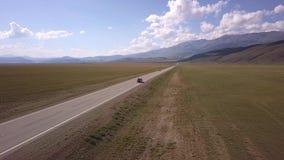Vue aérienne d'une équitation grise de voiture le long de la route par les champs plats Dans la hausse de fond les pentes du clips vidéos