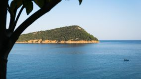 Vue aérienne d'une île dans les thassos Grèce avec les feuilles oranges et un bot dans le midle de la mer bleue images stock