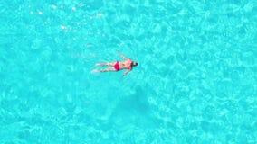 Vue aérienne d'une femme attirante faisant la course de sein en mer clair comme de l'eau de roche clips vidéos