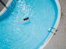 Vue aérienne d'une jeune fille dans le maillot de bain noir, dans la piscine bleue Images stock