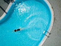 Vue aérienne d'une jeune fille dans le maillot de bain noir, dans la piscine bleue Image libre de droits