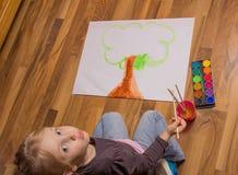 Peinture de petite fille avec des couleurs pour aquarelle Photo libre de droits